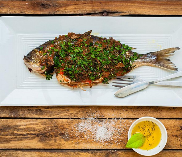 Fish on bakery paper with Extra Virgin Olive Oil