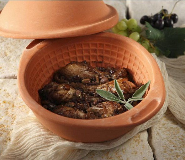 Chicken drumsticks in a ceramic pot with raisins and molasses